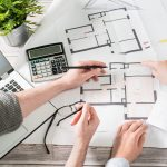 two people sit at a desk with a laptop and calculator working on the floor plan design for a new home.