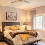 A comfortable looking bed in master bedroom with brown and yellow accents.
